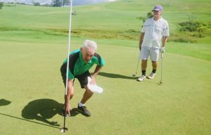 Chris Pottinger extracts his ball from the cup while playing partner Richard Clayton looks on_e
